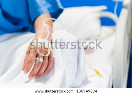 close up of iv drip in woman hand on bed in hospital - stock photo