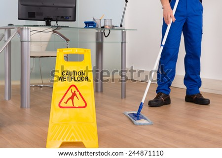 Close-up Of Janitor Mopping With Wet Floor Sign In Office - stock photo