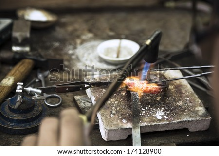 Close up of Jeweler crafting golden bracelet with flame torch. - stock photo
