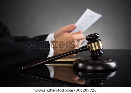 Close-up Of Judge Holding Document With Gavel At Desk - stock photo
