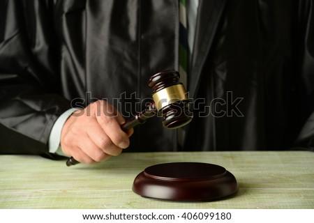 Close up of judge holding gavel - stock photo