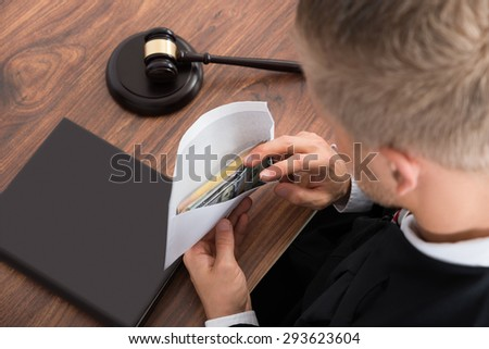 Close-up Of Judge Looking At Money At Desk In Courtroom - stock photo