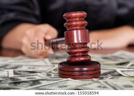 Close-up Of Judge Striking The Gavel Surrounded By Banknote - stock photo