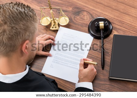 Close-up Of Judge Writing On Paper In Courtroom - stock photo