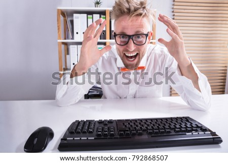 Close-up Of Keyboard In Front Of Pointing Happy Businessman Wearing Eyeglasses