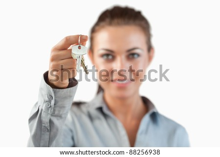 Close up of keys being held by female estate agent against a white background - stock photo