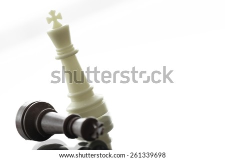 close up of king chess figure surrounded by a number of fallen black chess as strategy or leadership concept - stock photo