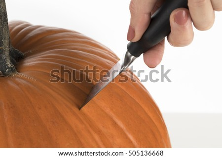 Close up of knife cutting into pumpkin for carving into jack o lantern