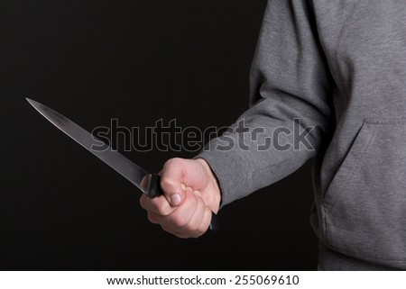 close up of knife in male hand over grey background - stock photo