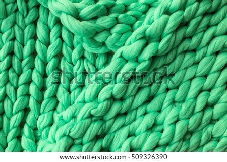 Close-up of knitted blanket, green merino wool background
