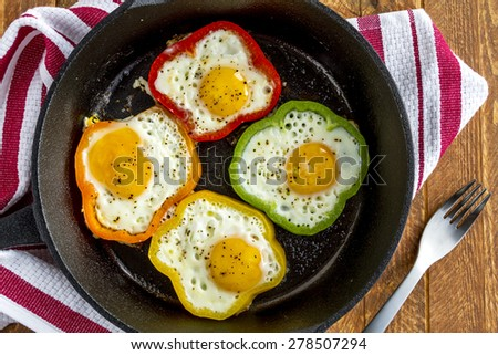 Close up of large cast iron skillet with fried eggs in green, yellow, red and orange bell peppers sitting on wooden table with fork and red striped towel - stock photo