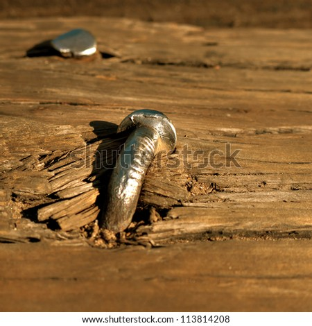 Close up of large nails driven into the wooden planks of an old railroad bridge in Grand Saline, Texas. - stock photo