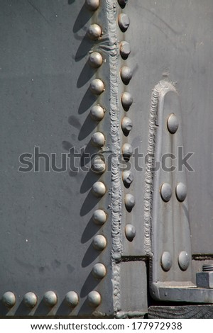 Close up of large train rivets and welded seam on old steam engine locomotive.