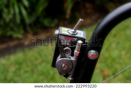 Close up of lawnmower switch on green grass background - stock photo