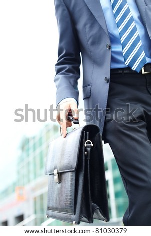 Close-up of leather briefcase in male hand - stock photo