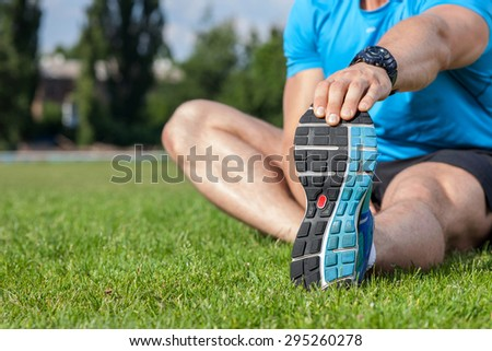 Close up of legs and torso of fit sportsman sitting on grass. He is stretching his left hand and doing warm-up.  There is copy space in left side - stock photo
