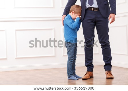 Close up of legs of busy father going to work. His small child is standing near him and crying. The father is embracing the boy with love. Copy space in left side - stock photo