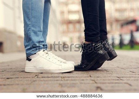 Close up of legs of couple kissing at city street with stone pavement. Man in blue jeans and white sporty sneakers and woman in black trousers and black leather boots