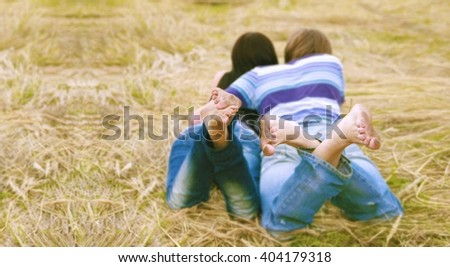 Close-up of legs of lying pair. Couple Relax barefoot enjoy nature in the green land dry yellow lawn or field. Empty space for inscription or other objects. - stock photo