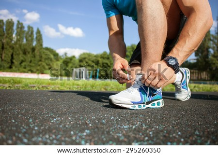 Close up of legs of sportsman tying the laces in stadium. There is copy space in left side - stock photo