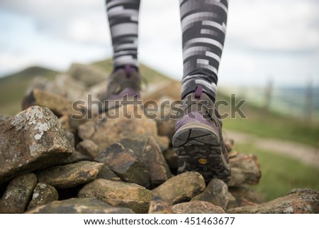 Close-up of legs of woman hiker walking on the mountain trail .Focus on hiking shoes.