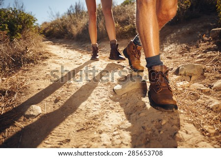 Close-up of legs of young hikers walking on the country path. Young couple trail waking. Focus on hiking shoes. - stock photo