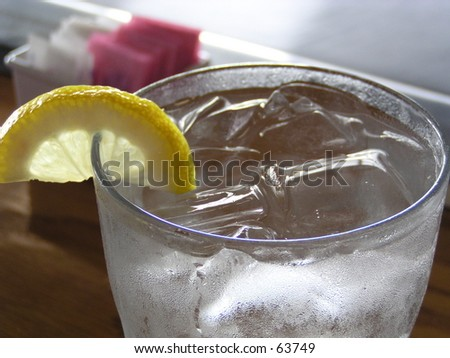 close up of lemon wedge in glass of ice water