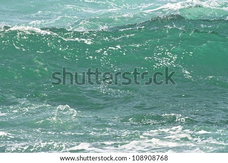 Close-up of light green translucent ocean wave - stock photo