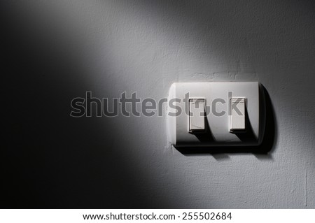 Close up of Light switch with sunlight and shadow on white background, turn on and off, copy space, In the dark - stock photo