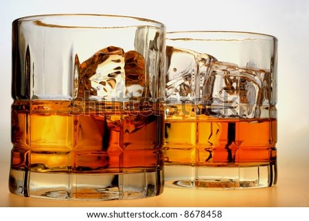 Close-up of liquor and ice in glasses on a white background.