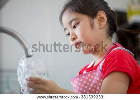 Close up of little Asian girl washing dishes in the kitchen