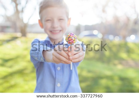 close-up of little boy holding colorful lollipop candy, shallow DOF, easter and spring concept - stock photo