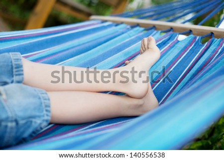 close-up of little child relaxing in hammock outdoors - stock photo