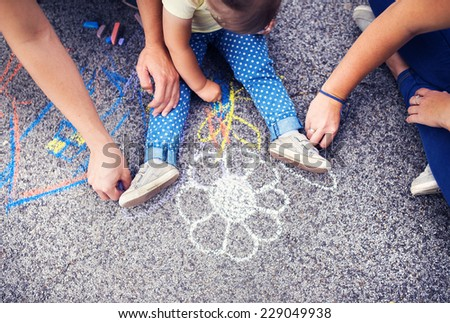 Close up of little girl and her parents drawing with chalks on the sidewalk - stock photo