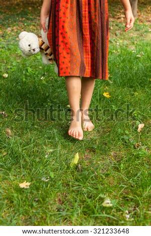 Close up of little girl feet walking on grass  - stock photo