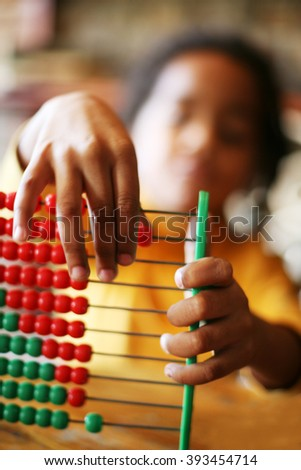 Close up of little girl hands accounting. Focus is on hands. - stock photo