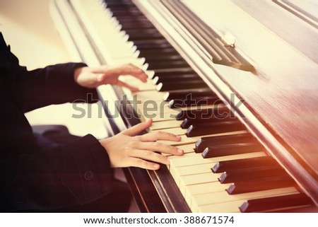 Close up of little girl hands playing piano - stock photo