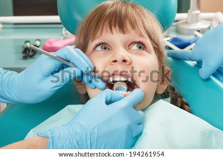 Close-up of little girl having her teeth checked by unidentified doctor - stock photo
