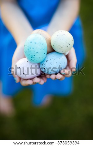 Close up of little girl holding colorful Easter eggs - stock photo