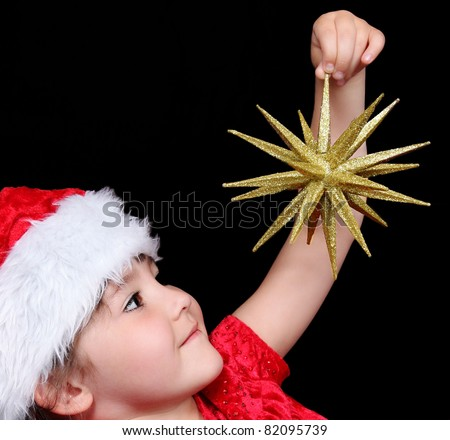 close-up of little girl in santa hat holding up golden christmas star. isolated on black - stock photo