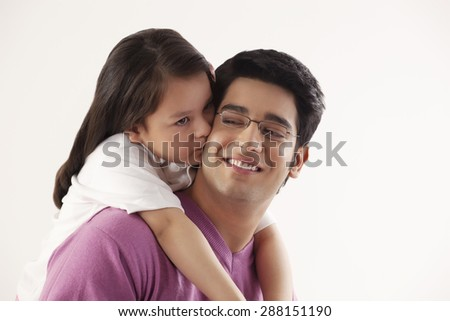 Close-up of little girl kissing her father - stock photo