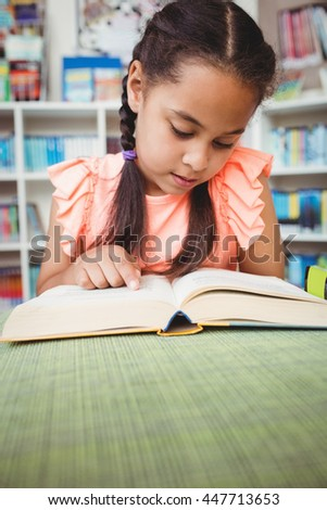 Close up of little girl reading a book in the library