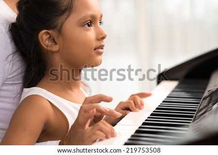 Close-up of little Indian girl playing the piano - stock photo