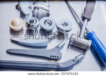 close up of lots of parts for transplantation of leg joints and tools for surgical operations on replacement of joints lie against a metal surface