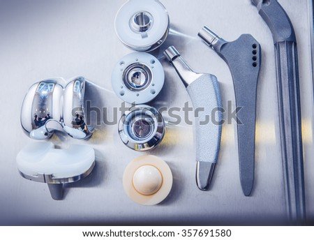 close up of lots of parts for transplantation of the joints of the feet lie against a metal surface - stock photo