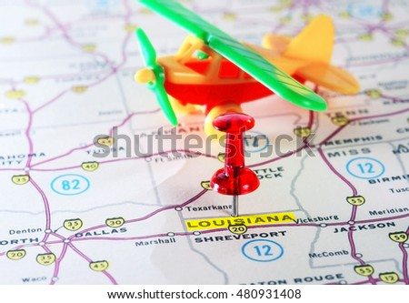 Close up of  Louisiana USA map with red pin and airplane toy - Travel concept