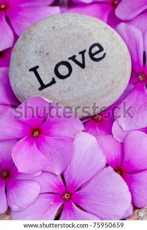 close up of 'love' stone amongst pink flowers