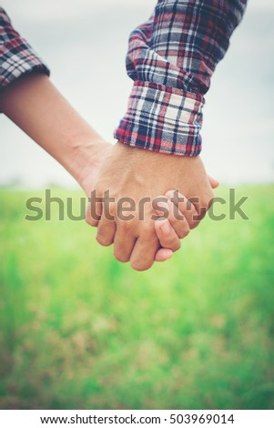 Close Up of loving hipster couple holding hands while walking at meadows field.