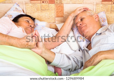 Close up of loving senior couple relaxing in bed. - stock photo