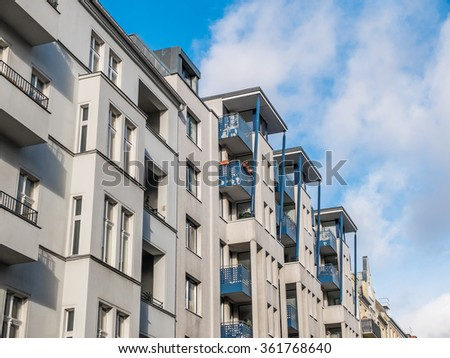 Close Up of Low Rise Residential Apartment Building with Balconies and Modern Design Features, Illuminated by Bright Sunlight with Blue Sky and Clouds in Background
